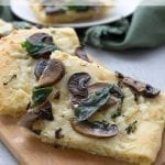 Titled image of keto flatbread with mushrooms and age on a wooden cutting board.