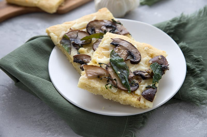 Two slices of keto flatbread topped with mushrooms, sage, and fontina cheese on a white plate.