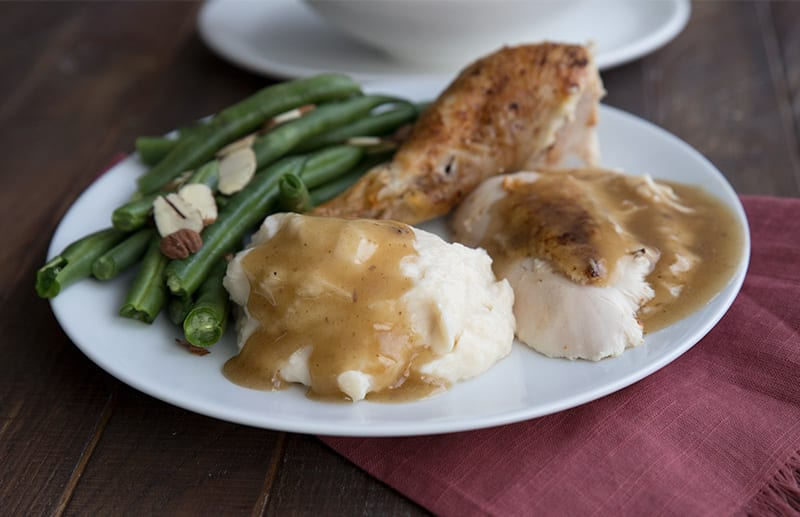 Roast turkey with keto gravy, mashed cauliflower, and green beans on a white plate over a red napkin.