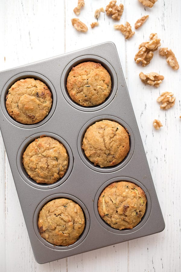 Top down photo of morning glory muffins in the pan with some walnuts, on a white table