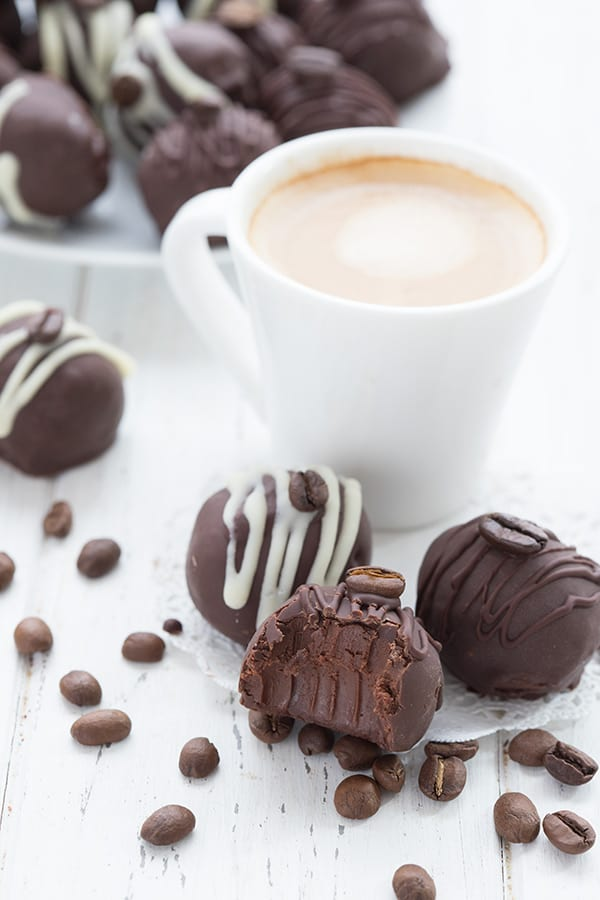 Keto sugar free chocolate truffles on a white table with a shot of espresso in a white cup