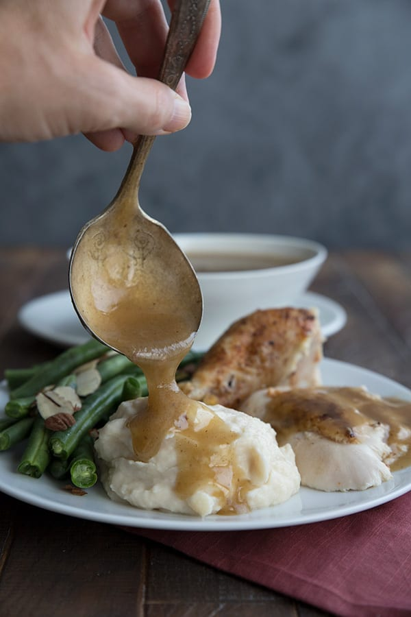 Pouring keto gravy from a ladle onto mashed cauliflower.