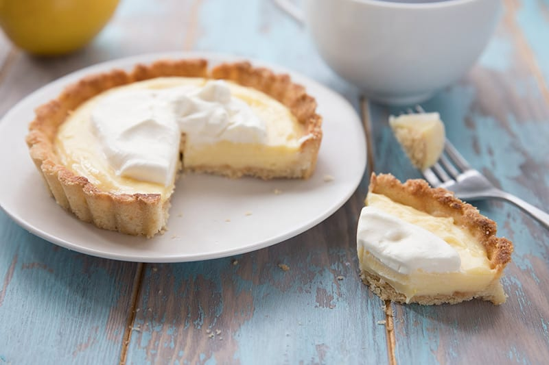 Keto Lemon Curd Tart for Two on a white plate over a blue wooden table.
