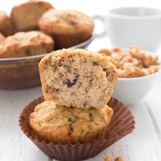Titled Image of Keto Morning Glory Muffins. One muffin cut open sits on top of another muffin in a brown wrapper.