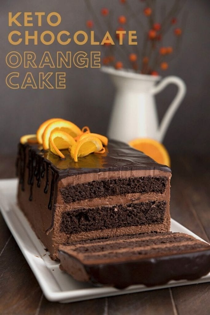 Titled image of keto chocolate orange layer cake on a white platter, with one slice cut out.