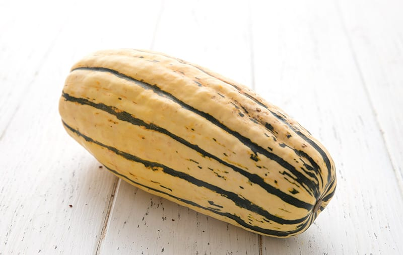 A whole uncooked delicata squash on a white wooden table.
