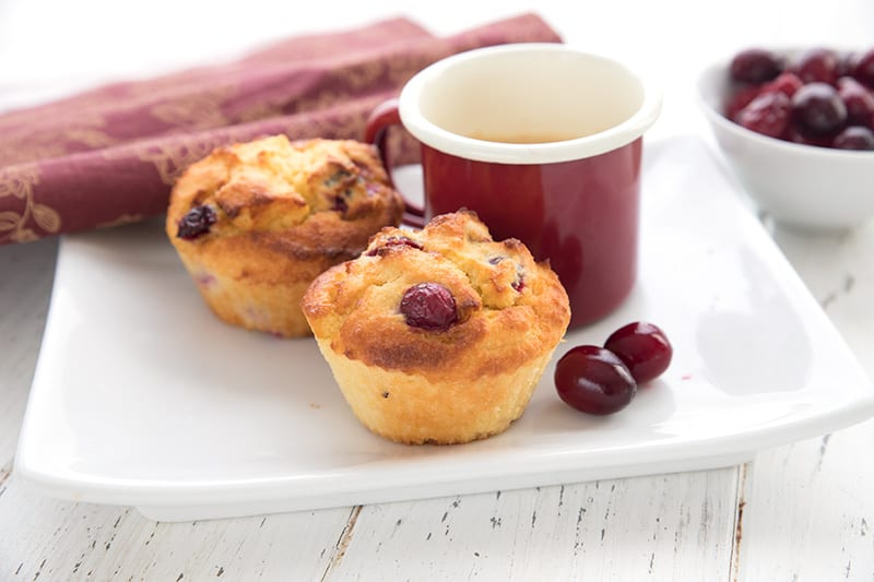 A white plate with two cranberry muffins and a cup of red coffee