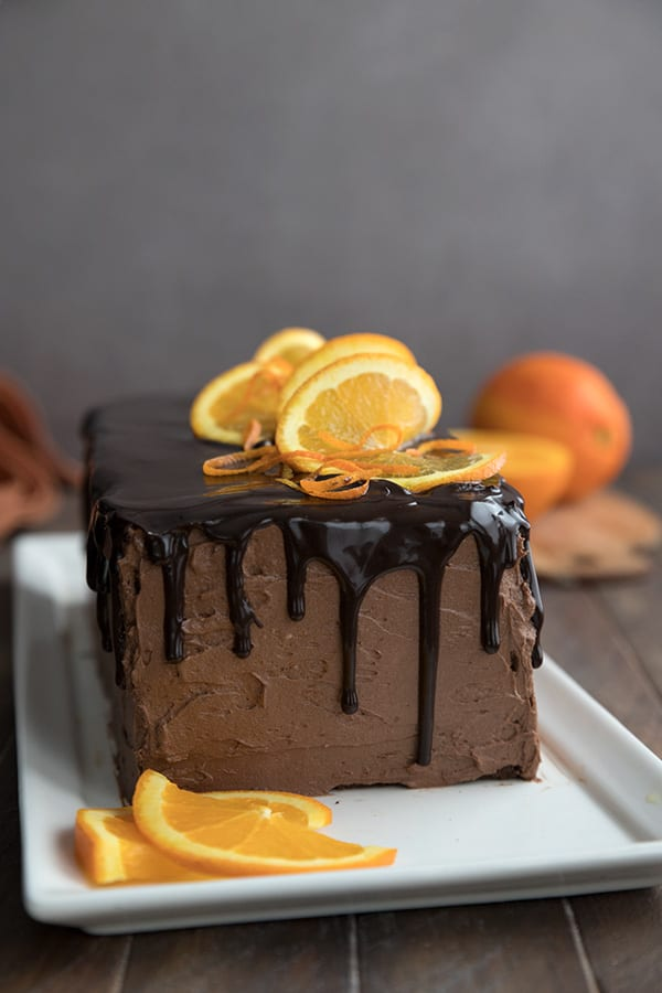 Keto chocolate orange layer cake on a white platter with slices of orange in front