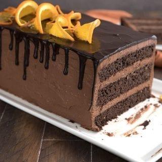Close up shot of keto chocolate orange layer cake on a white platter