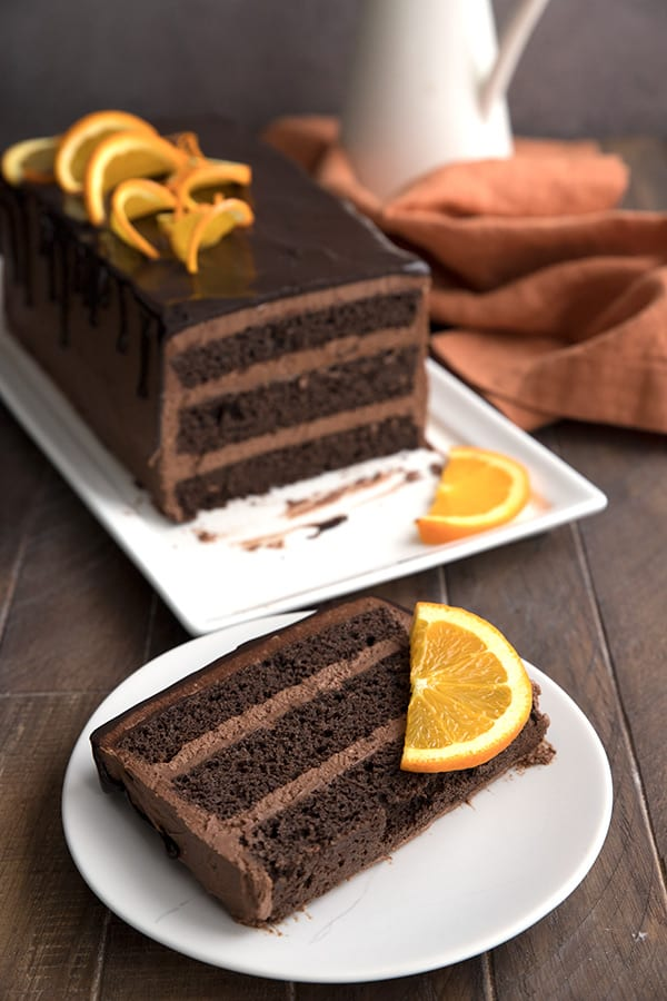 A slice of keto chocolate orange cake on a white plate, in front of the rest of the cake on a rectangular cake platter.