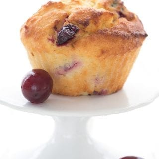 A keto cranberry orange muffin on a white cupcake stand with two fresh cranberries.