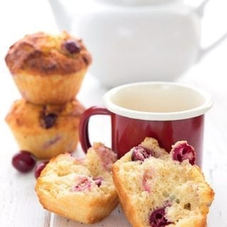Titled image of keto cranberry orange muffins on a white table with a red cup of coffee. The muffin in front is broken up to show the inside.