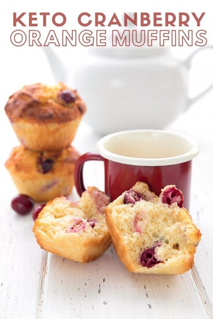 Image titled Keto Cranberry Orange Muffins on a white table with a red cup of coffee.  The front muffin is broken to show the inside.
