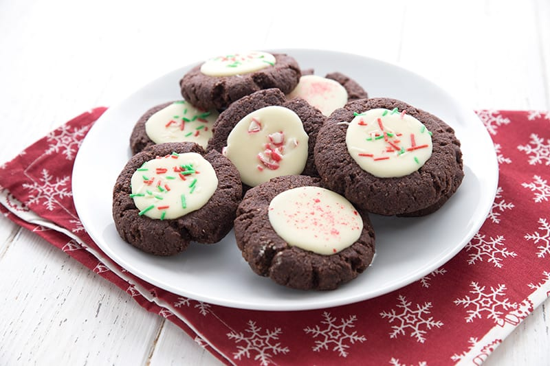 A white plate filled with keto chocolate peppermint cookies over a red napkin with white snowflakes.