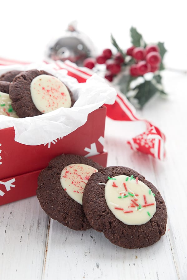 Two keto peppermint thumbprint cookies site in front of a gift box filled with more cookies and some holly in the background.