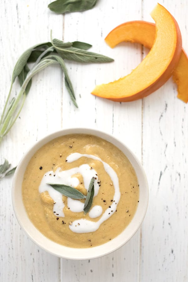Top down photo of keto pumpkin soup in a white bowl on a white wooden table, with sliced ​​pumpkin leaves and sage