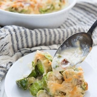 Titled image for Brussels Sprouts Casserole, with a spoon dishing some of the creamy sauce over the plate.