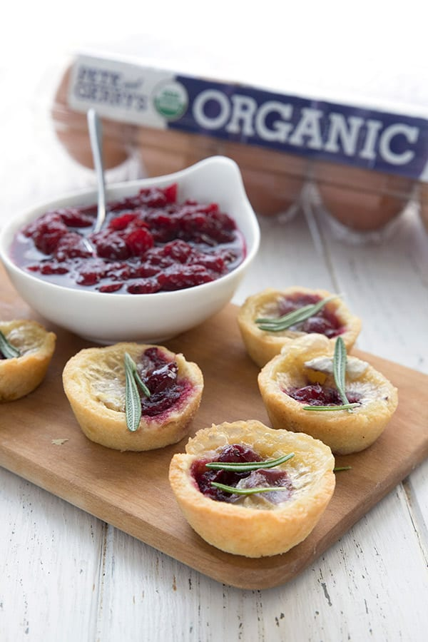 Mini ket tarts filled with brie and sugar-free cranberry sauce, with organic eggs in the background