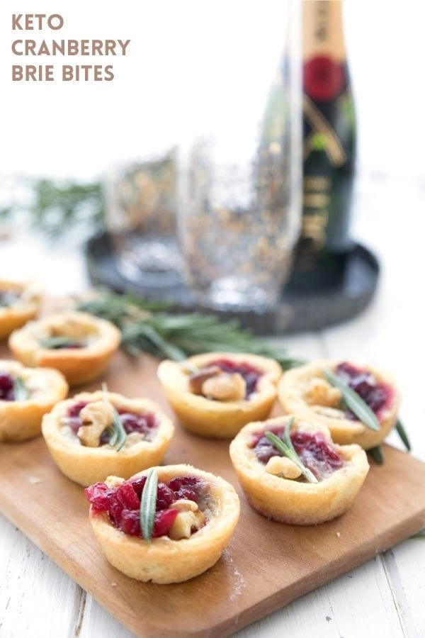 Titled image of Keto Cranberry Brie Bites on a wooden cutting board with champagne and glasses in the background.