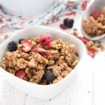 A close up shot of a bowl of keto granola, with a metal scoop in the background.