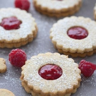 Titled image of keto Linzer cookies on a grey table with raspberries sprinkled around