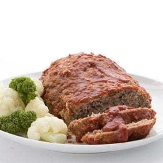 Titled Image of a classic keto meatloaf on a white plate with cauliflower and broccoli