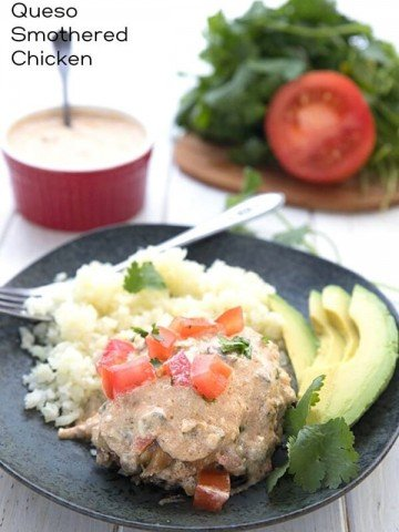 Titled image for Keto Slow Cooker Smothered Chicken, with a piece of chicken on a black plate with cauliflower rice and avocado.