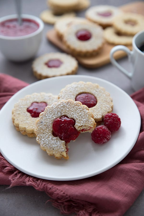 Three keto Linzer cookies on a white plate over a red napkin, with more cookies in the background and a bowl of the raspberry filling