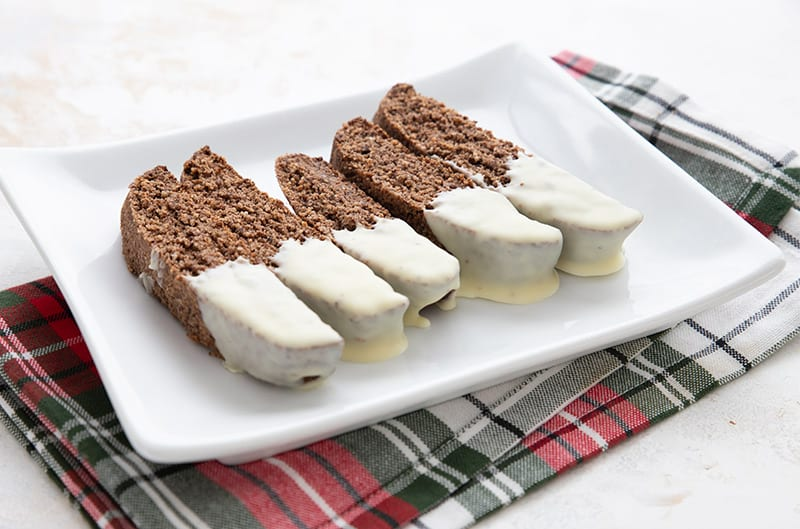 A white platter filled with low carb gingerbread biscotti over a plaid Christmas napkin.
