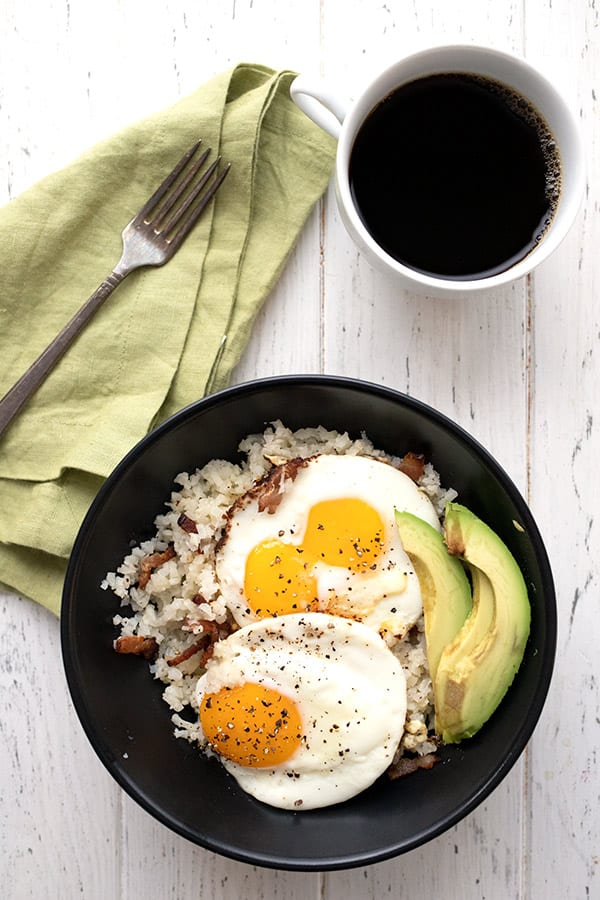 Top down photo of keto breakfast grits with bacon, fried eggs, and avocado in a black bowl. A cup of coffee and a green napkin with a fork are also featured.