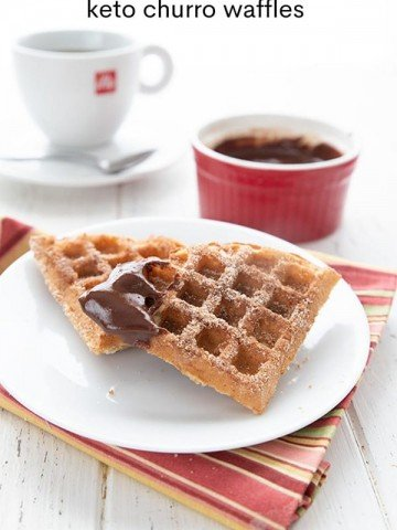 Titled image of keto churro waffles on a white plate. The top waffle has been dipped in chocolate sauce.