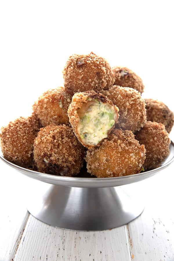 A metal stand piled with keto fried cheese bites, with one broken open to show the inside.