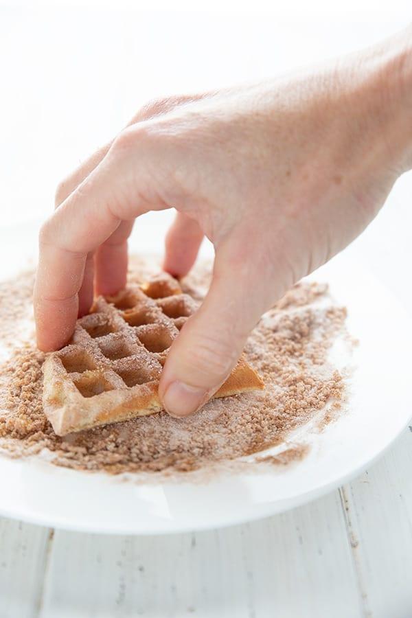 A hand dipping keto churro waffles in cinnamon and sweetener