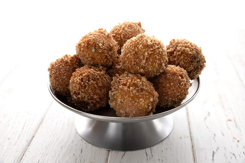 A metal cake stand full of keto fried cheese bites on a white wooden table.
