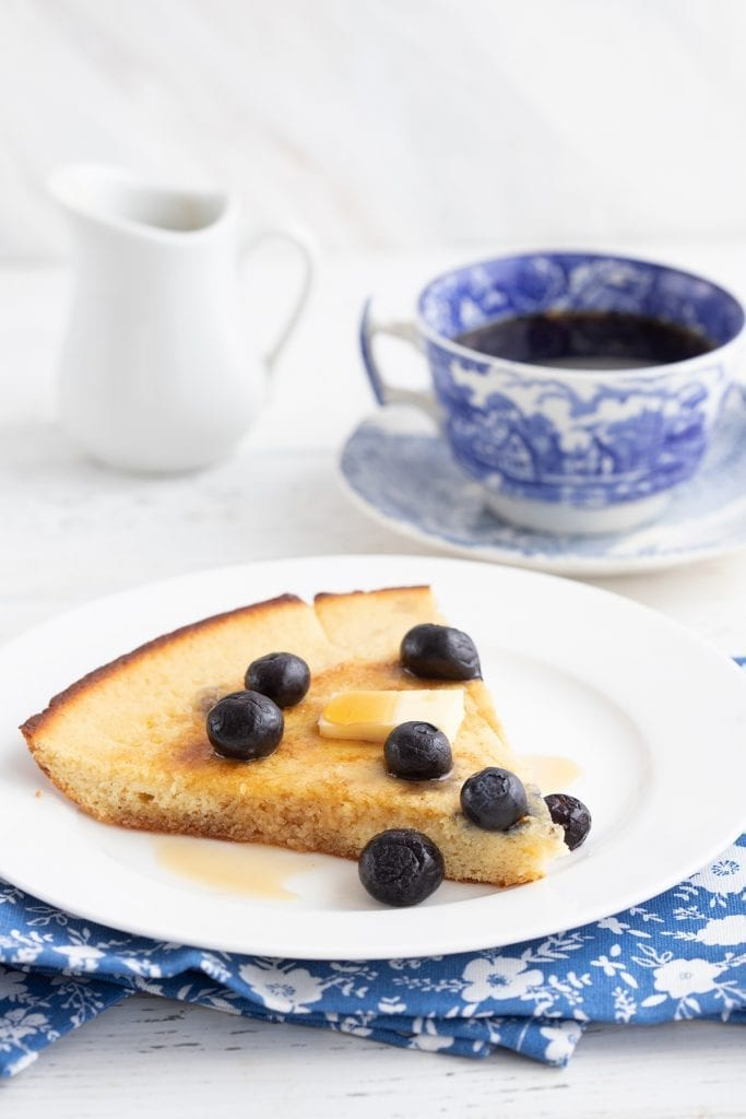A piece of a keto baked pancake on a white plate over a blue patterned napkin, with butter and syrup on top.