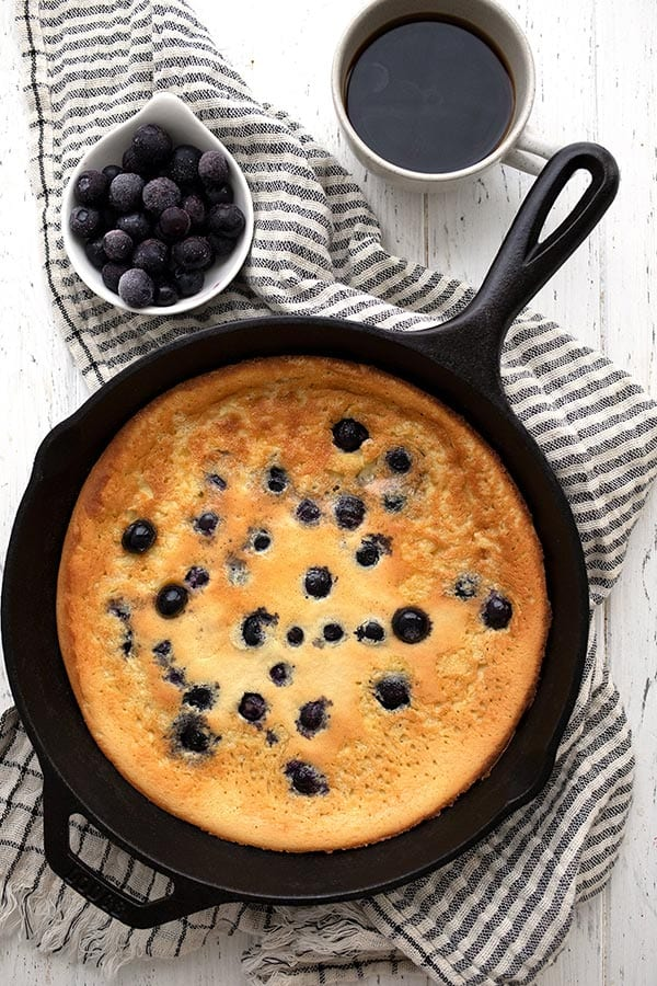 Top down image of a keto deep dish pancake in a cast iron skillet on a white wooden table.