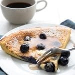 A fork taking a bite out of a keto blueberry pancake on a white plate with a cup of coffee in behind.