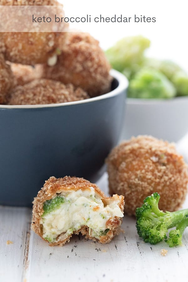 Titled image of keto fried cheese balls on a white table. One is broken open to show the inside, the rest are in a blue bowl.