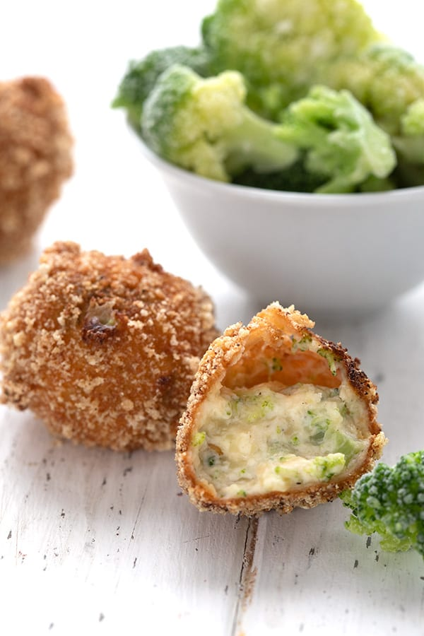 Close up shot of keto broccoli cheddar bites in front of a bowl of broccoli