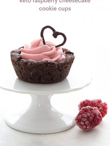 Titled image of a keto chocolate cookie cup filled with raspberry cheesecake on a white cupcake stand.