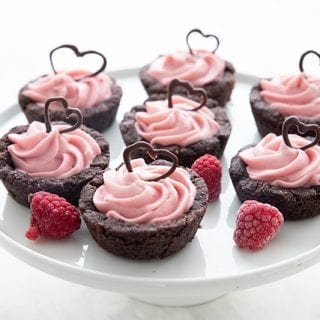 Keto Raspberry Cheesecake Cookie Cups on a white cake stand with raspberries