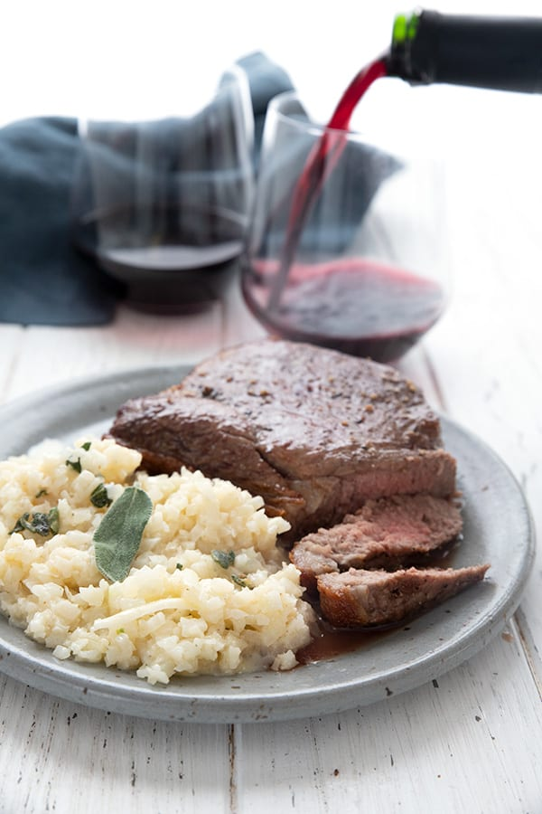 A plate full of steak and cheesy cauliflower risotto with a glass of wine being poured in the background.