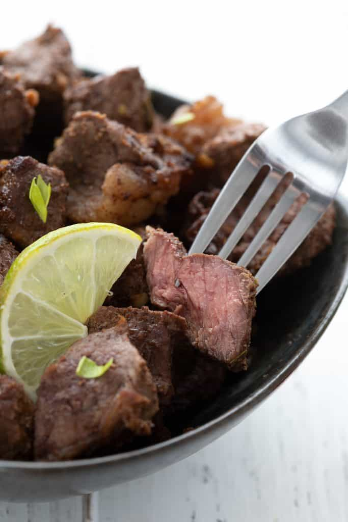 Close up shot of air fryer steak bites in a bowl, with a fork lifting one out. The bite is cut open to show the pink inside.