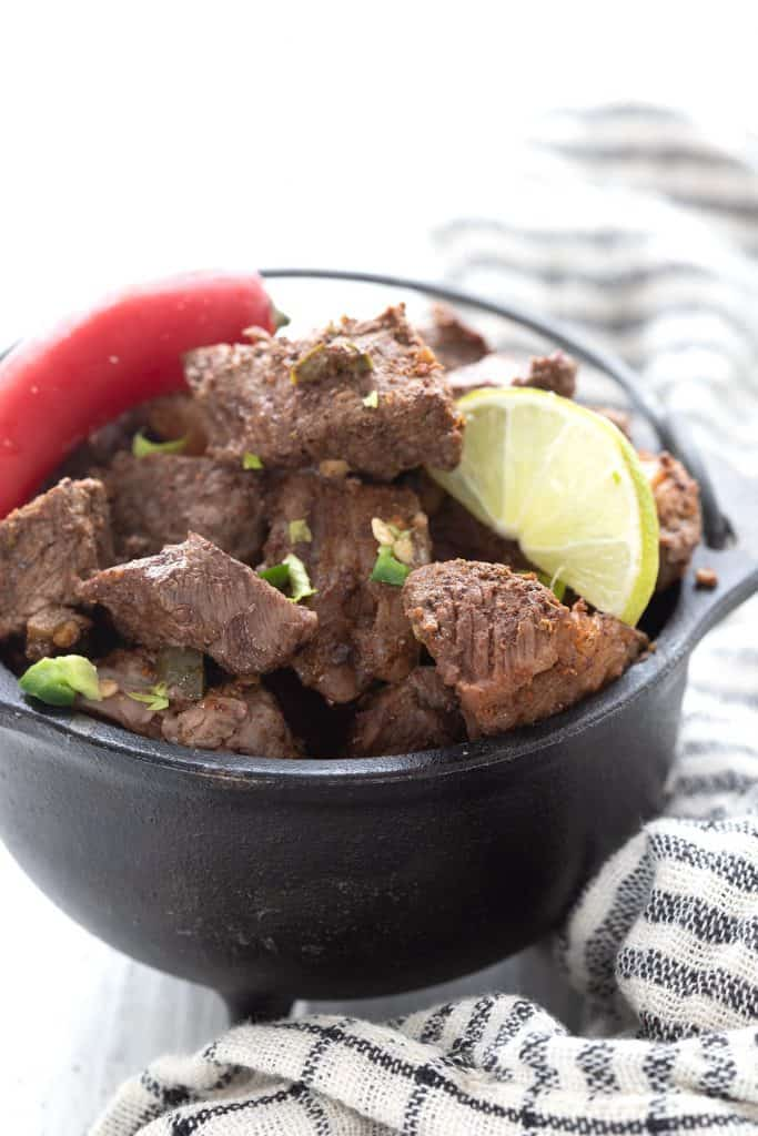 A small cast iron pot filled with keto steak bites, topped with a lime and a chili.