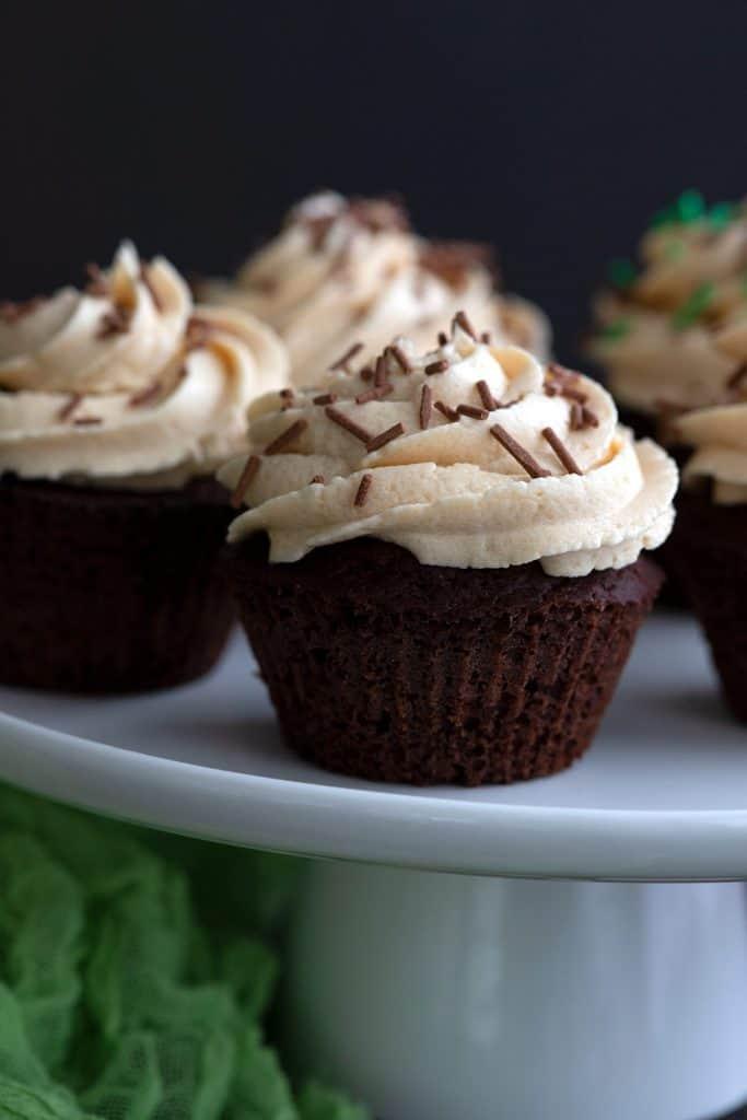 Close up shot of a keto Irish Cream Cupcake on a white cake plate.