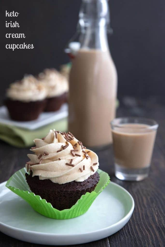 Titled image of a keto Irish Cream cupcake on a white plate, with the bottle of sugar free Irish Cream in behind.
