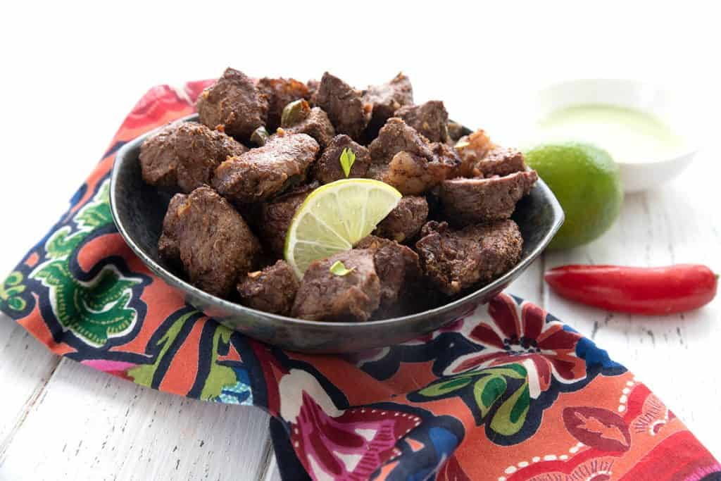 A black bowl of keto air fryer steak bites over a colourful printed napkin.