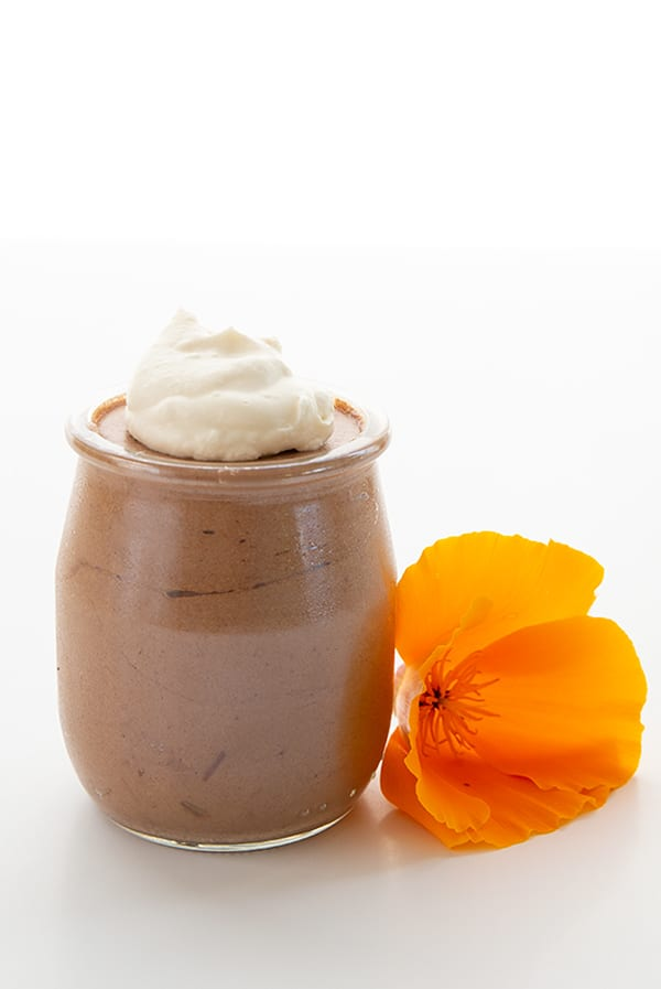 A jar of keto chocolate mousse with whipped cream on top beside an orange flower