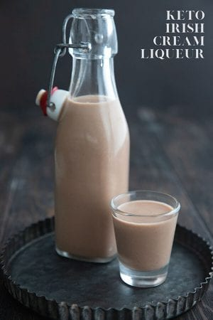Titled image of a shot glass full of keto Irish Cream on a tray with the bottle full of the sugar-free liqueur.