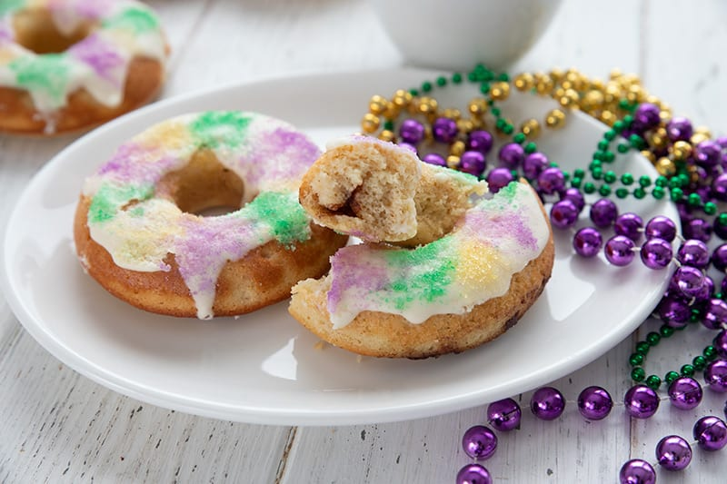 Close up shot of a plate with keto king cake donuts, one broken open to show the cinnamon filling.